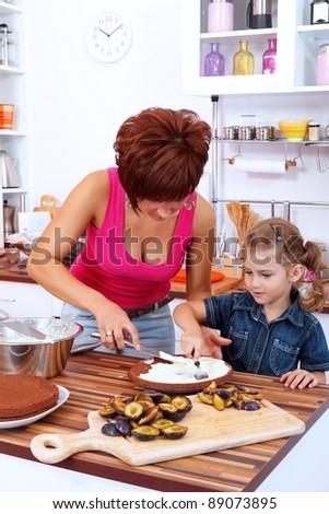 Mother and daughter making a cake with damson plums in the kitchen