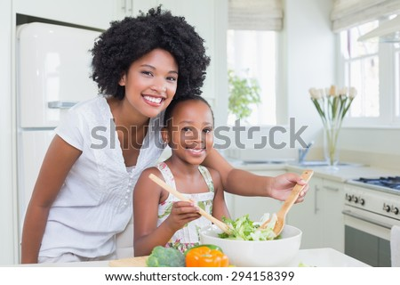 Mother and daughter making a salad together at home in the kitchen - stock photo