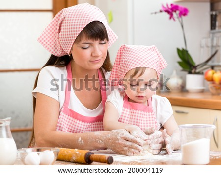 Mother and daughter making cookie dough together at kitchen - stock photo