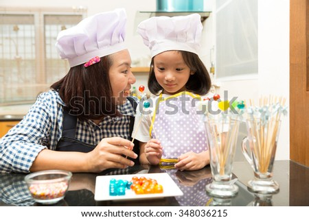 Mother and daughter making jelly candy in the kitchen in the kitchen