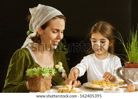 Mother and daughter making pasta at home. - stock photo