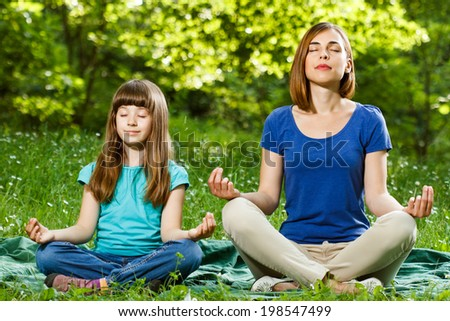 Mother and daughter meditating together,Mother and daughter meditating - stock photo