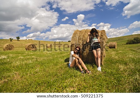 Mother and daughter near a bale of straw