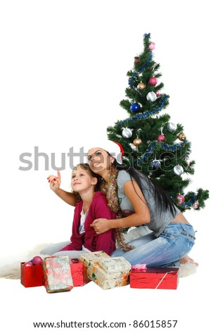Mother and daughter near a christmas tree with gifts, isolated on a white background - stock photo