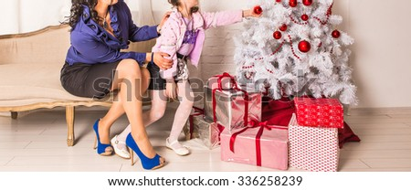 Mother and daughter near Christmas tree