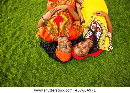mother and daughter of African ethnicity lying down on a grass - stock photo
