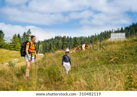 Mother and daughter on a mountain hike in the Alps, having fun and spending quality time together, with huts and cows in the background. Active parenting, fun childhood and family bonding concept.  - stock photo