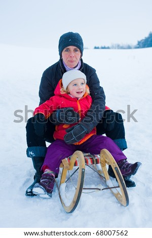 mother and daughter on a sled - stock photo