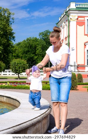 mother and daughter on a walk on a hot sunny day - stock photo