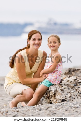 Mother and daughter on beach - stock photo