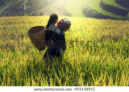 Mother and daughter on cornfield with little girl getting a piggyback ride on her back