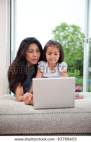 Mother and daughter on couch using laptop - stock photo