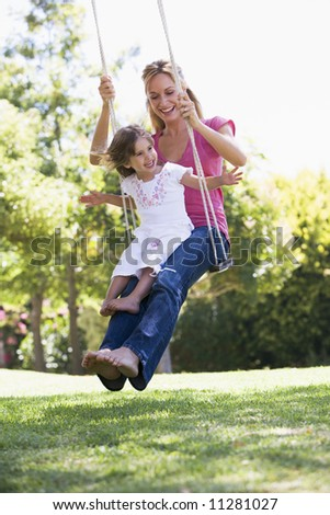 Mother and daughter on garden swing - stock photo