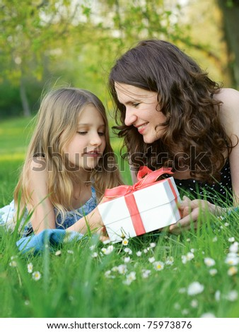 Mother and daughter on green grass with a gift box - stock photo