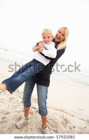 Mother And Daughter On Holiday Having Fun On Winter Beach