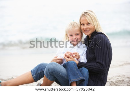 Mother And Daughter On Holiday Sitting On Winter Beach - stock photo