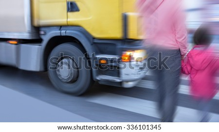 Mother and daughter on pedestrian crossing when big truck is passing - stock photo