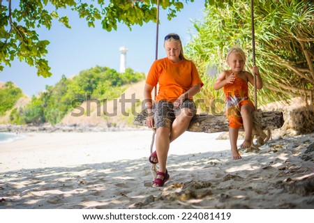 Mother and daughter on rope swing under palm trees on tropical beach with lighthouse on back - stock photo
