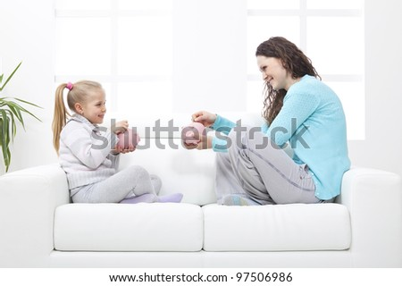Mother and Daughter on sofa learn about savings - stock photo