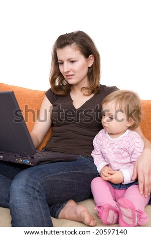 mother and daughter on sofa with laptop - stock photo
