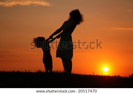 Mother and daughter on sunset watching on sky - stock photo