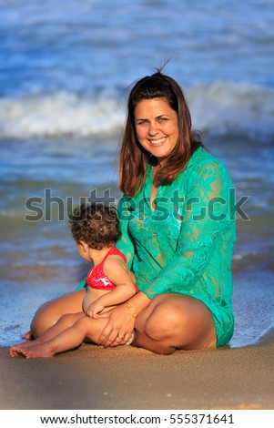 Mother and daughter on the beach playing on the water