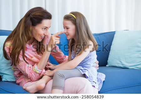 Mother and daughter on the couch at home in the living room - stock photo