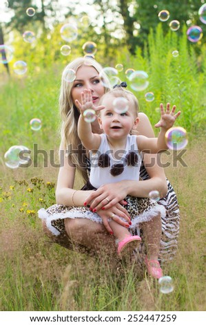 Mother and daughter on the nature of playing with air bubbles - stock photo