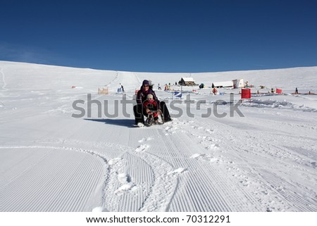 mother and daughter on the sled - stock photo