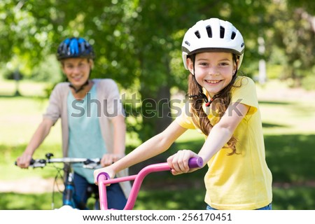 Mother and daughter on their bike on a sunny day - stock photo