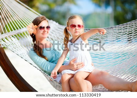 Mother and daughter on tropical vacation relaxing in hammock - stock photo