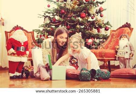 Mother and daughter opening Christmas presents,shallow depth of field - stock photo