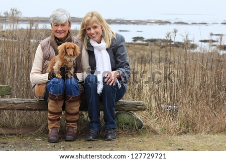 Mother and daughter outside with a dachshund puppy. - stock photo