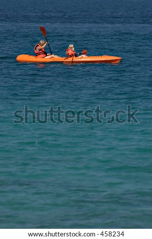 Mother and daughter paddling a kayak in the ocean off Perhentian Island, Malaysia - stock photo