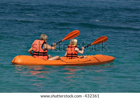 Mother and daughter paddling a kayak on the ocean - stock photo