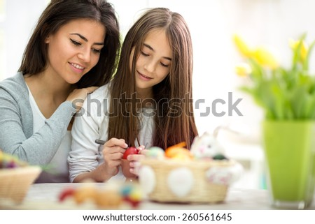 Mother And Daughter Painting Easter Eggs at home  - stock photo