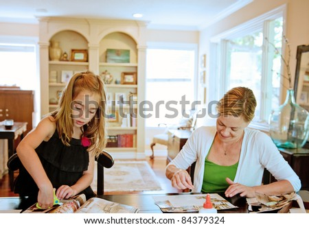 Mother and daughter pasting a collage together in their family room at home - stock photo