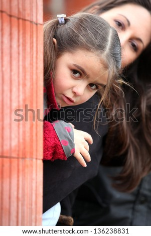 Mother and daughter peering from behind brick wall - stock photo