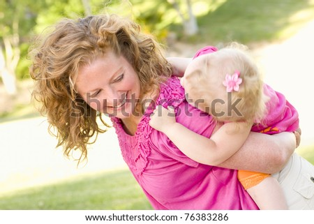 Mother and Daughter Piggyback Ride in the Park. - stock photo