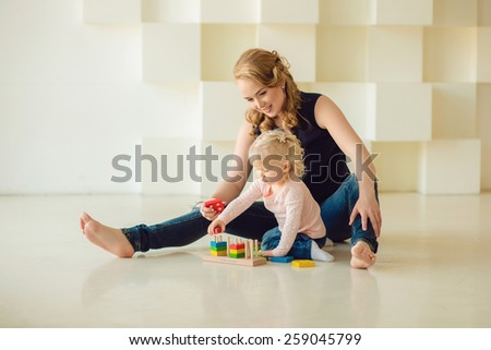 Mother and daughter play sitting on the floor - stock photo