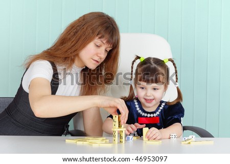 Mother and daughter play together at the table