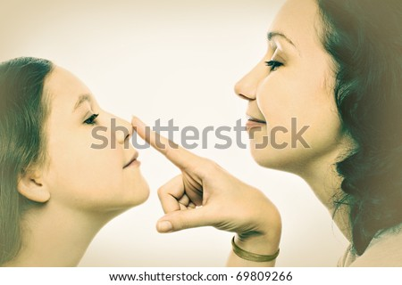 Mother and daughter playful portrait. Two profiles of woman and child girl. - stock photo