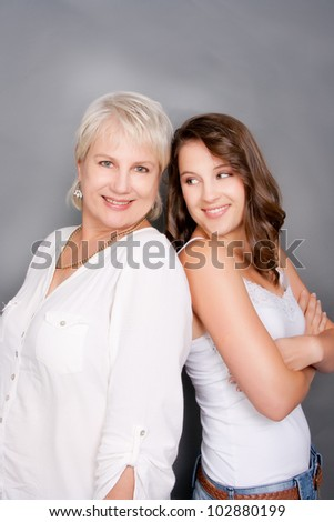 Mother and daughter playfully happy standing back to back - stock photo