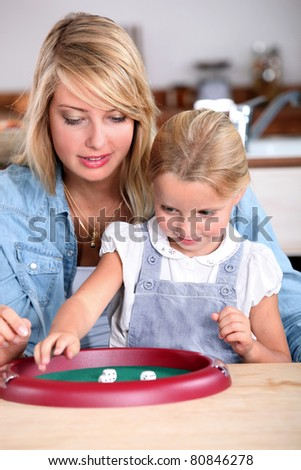 Mother and daughter playing a game - stock photo
