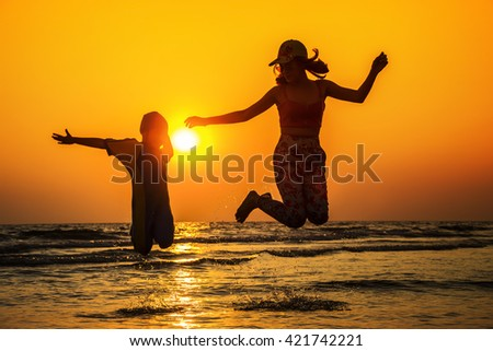 mother and daughter playing beach silhouette blur background