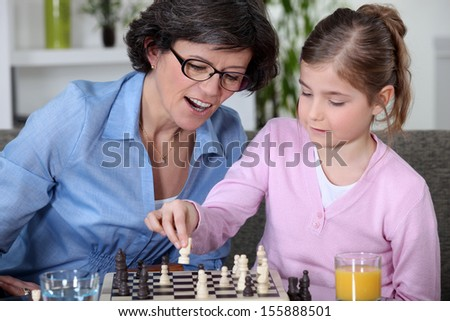 Mother and daughter playing chess - stock photo