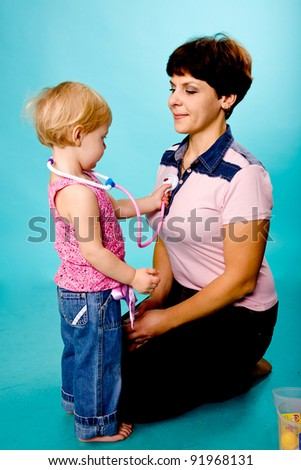 Mother and daughter playing doctor and patient. Isolated on turquoise - stock photo