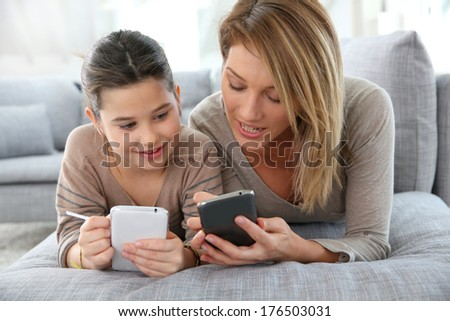 Mother and daughter playing games with smartphone - stock photo