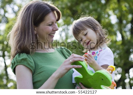 Mother and daughter playing in park together