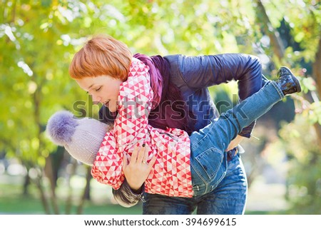 Mother and daughter playing in the Park, cool weather, horizontal. - stock photo